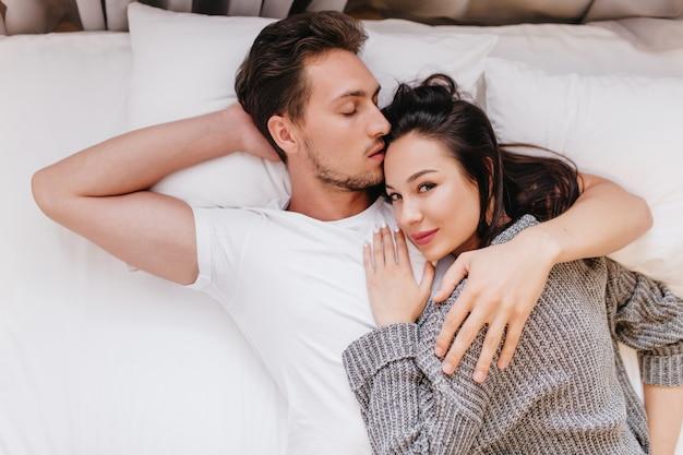 Foto interna de um cara preguiçoso em uma camiseta branca beijando uma namorada de cabelo preto