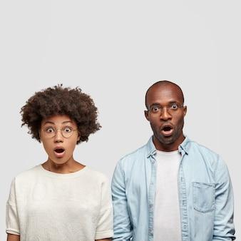 Foto interna de um casal afro-americano aterrorizado recebendo a conta