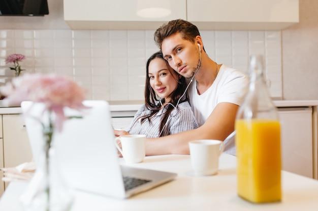 Foto interna de um casal apaixonado usando um laptop, enquanto relaxa na cozinha