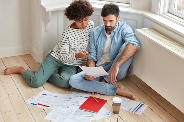 Foto interna de um casal de família mestiça analisa dados e desenvolve um novo projeto de inicialização