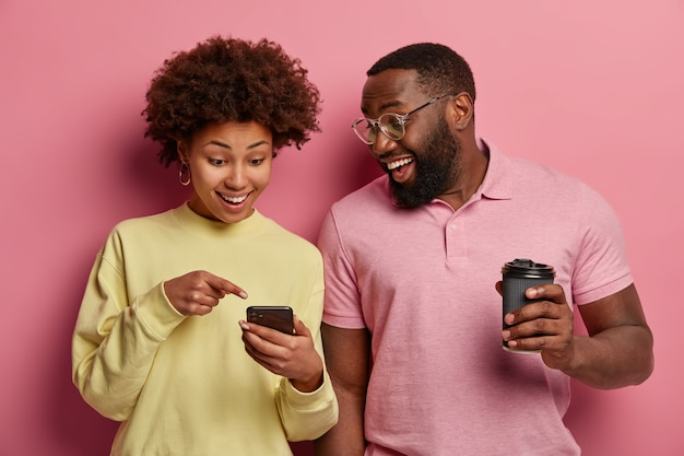 Foto interna de um casal feliz de pele escura tomando café para viagem, assistindo ou lendo informações on-line em um gadget moderno e vestindo roupas em tons pastéis