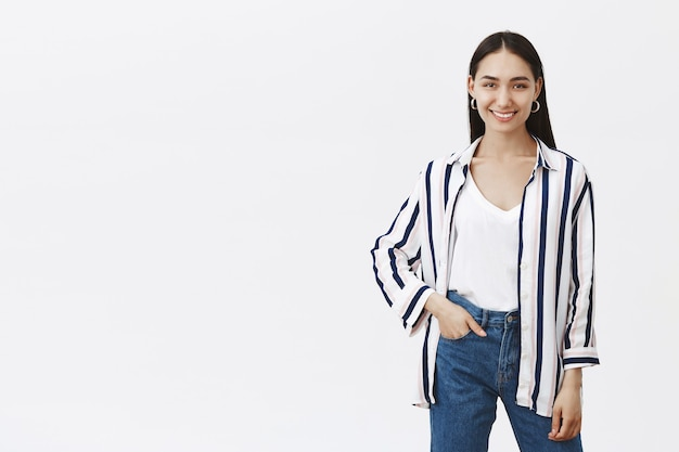 Foto interna de um designer elegante e criativo com uma blusa listrada e jeans estilosos, segurando a mão no bolso enquanto sorri amplamente, em uma pose relaxada e confiante sobre uma parede cinza