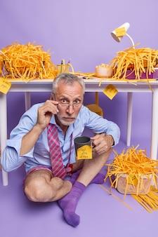 Foto interna de um empresário de cabelos grisalhos usando camisa formal e gravata no pescoço funciona remotamente em um escritório caseiro aconchegante, sentado no chão, tem poses para o café perto da área de trabalho