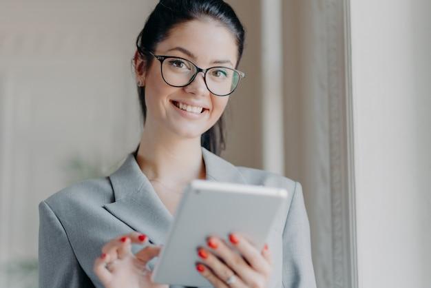 Foto interna de um empresário feliz e moreno lendo um livro eletrônico em um tablet digital moderno, lendo notícias financeiras na internet durante o intervalo do trabalho, usando óculos ópticos, traje cinza, poses internas