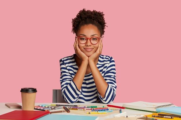 Foto interna de um estilista de pele escura com cabelo crespo, tocando as bochechas com as duas mãos, usando roupas listradas, trabalhando em um novo projeto criativo, poses no local de trabalho contra uma parede rosa