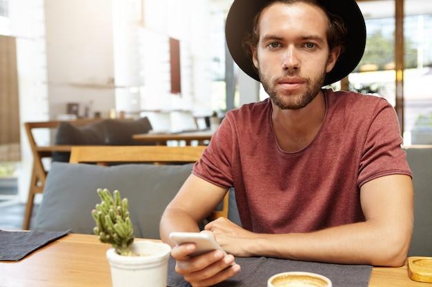 Foto interna de um estudante estiloso usando um chapéu preto enviando mensagens de texto para amigos nas redes sociais, usando wi-fi grátis em seu celular durante o café da manhã em um café com interior moderno, olhando