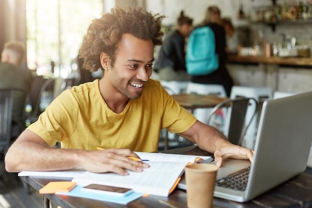 Foto interna de um estudante feliz do sexo masculino com cabelo encaracolado vestido casualmente sentado na cafeteria, trabalhando com tecnologias modernas, enquanto estuda, olhando com um sorriso no caderno recebendo mensagem de um amigo