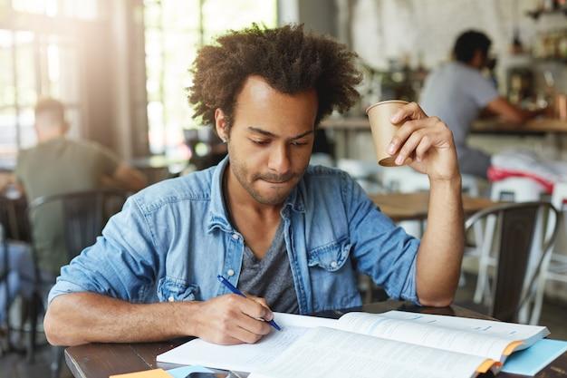 Foto interna de um estudante negro bonito sério tomando café enquanto trabalhava em casa, escrevendo no caderno usando uma caneta, olhando as anotações com uma expressão focada e procurando lábios