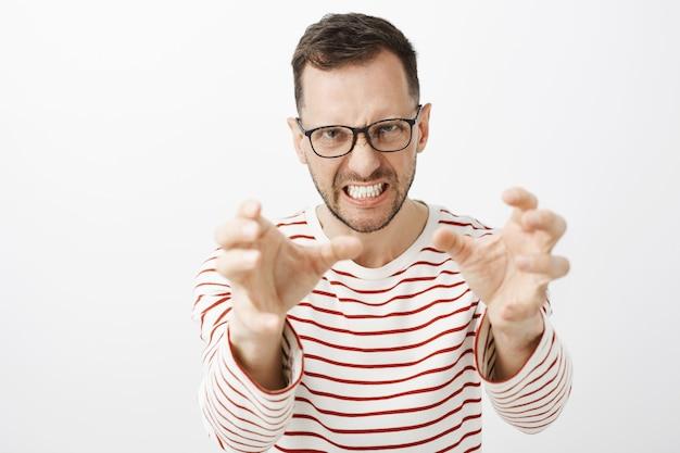 Foto interna de um europeu zangado e irritado de óculos escuros, puxando as mãos em direção
