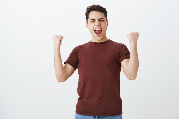 Foto interna de um fã de futebol bonito triunfante positivo em uma camiseta vermelha casual