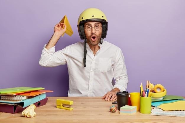 Foto interna de um funcionário surpreso sentado na mesa do escritório
