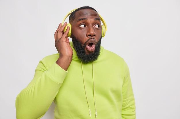 Foto interna de um homem adulto barbudo em choque mantém a boca aberta e mantém a mão em fones de ouvido sem fio usa um moletom verde parece distante, isolado na parede branca ouve uma nova música da lista de reprodução
