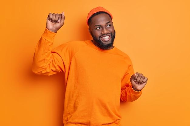 Foto interna de um homem afro-americano de pele escura e positivo apertando as mãos e movendo danças despreocupadas com uma expressão feliz