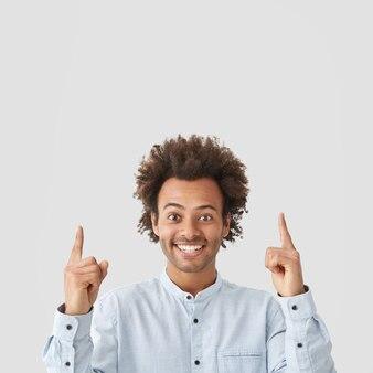 Foto interna de um homem afro-americano feliz e satisfeito com cabelo encaracolado, sorriso largo e brilhante, aponta para cima com os dois dedos indicadores