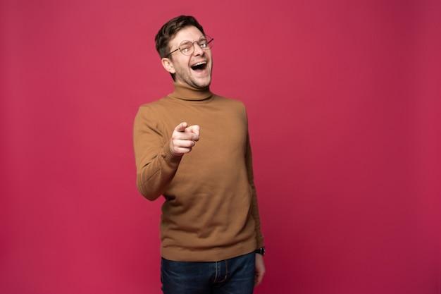 Foto interna de um homem alegre de óculos e roupas casuais indica felicidade para você