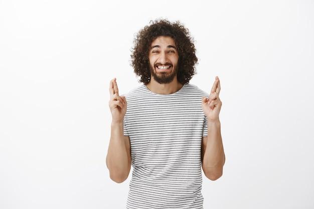 Foto interna de um homem ansioso e crente de barbudo oriental com penteado afro, levantando os dedos cruzados e fazendo uma careta de nervosismo, querendo realizar o desejo