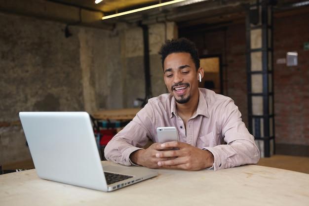 Foto interna de um homem bonito de pele escura com barba trabalhando remotamente com um laptop moderno em um espaço de coworking, tendo um vídeo chat com parceiros em seu smartphone e sorrindo alegremente para a câmera