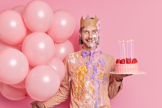 Foto interna de um homem bonito e alegre comemorando aniversário manchado de creme com bolo delicioso e balões se divertindo na festa de aniversário isolada na parede rosa
