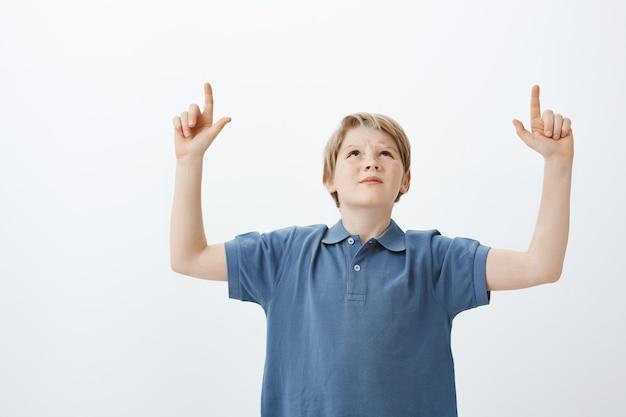 Foto interna de um homem duvidoso descontente com cabelo loiro, olhando e apontando para cima com o dedo indicador levantado, carrancudo, inseguro e irritado com os vizinhos barulhentos