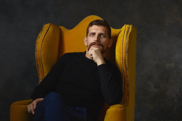 Foto interna de um homem elegante com barba por fazer vestido de preto relaxando em uma poltrona amarela e esfregando a barba sentado contra uma parede em branco com espaço de cópia para seu conteúdo
