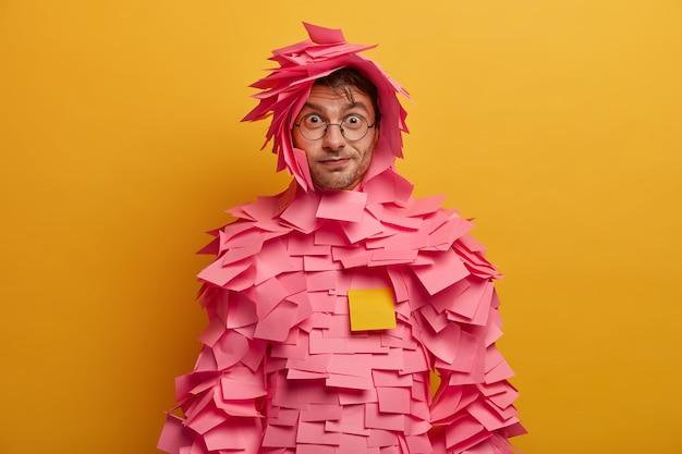 Foto interna de um homem engraçado surpreso parece através de óculos transparentes, usa fantasia de papel tem olhar direto isolado sobre a parede amarela. cara maravilhada, vestida com roupa feita de notas adesivas