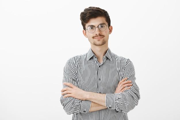 Foto interna de um homem europeu intenso descontente com barba e bigode em óculos da moda, de mãos cruzadas no peito e olhando com espera, sendo ofendido e querendo ouvir um pedido de desculpas