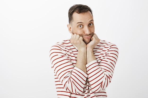 Foto interna de um homem gay emotivo e fofo usando um pulôver listrado, apoiando o rosto nas palmas das mãos e fazendo uma careta de pato com lábios fazendo beicinho