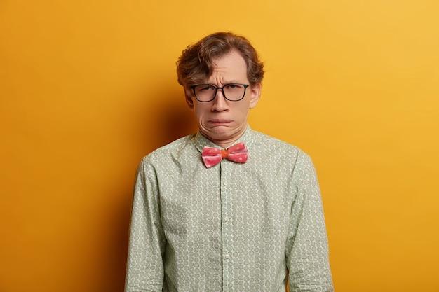 Foto interna de um homem insatisfeito com um sorriso afetado, uma expressão carrancuda, um rosto infeliz, ouve algo desagradável, usa óculos ópticos e roupa formal, posa em uma parede amarela