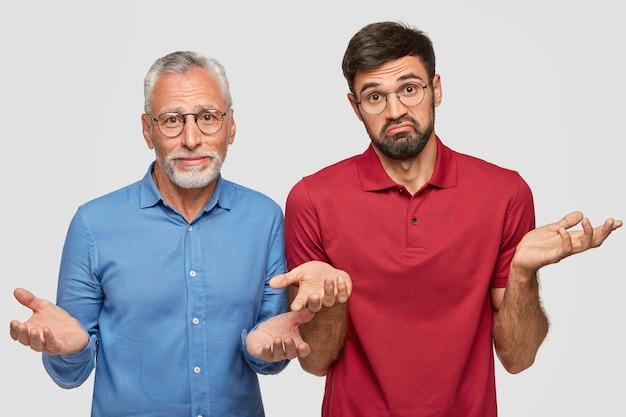 Foto interna de um homem maduro e intrigado e seu filho adulto, encolhe os ombros, não consegue tomar uma decisão, estando com a barba por fazer, fique perto um do outro contra a parede branca. então, o que fazer nesta situação?