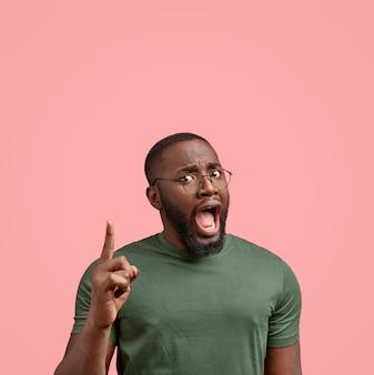 Foto interna de um homem negro com a barba por fazer indignado abre a boca amplamente e expressa emoções negativas