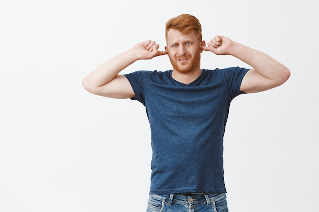 Foto interna de um homem ruivo descontente sentindo desconforto, franzindo a testa e fazendo caretas, cobrindo os ouvidos com tampões de ouvido e olhando para o lado, ouvindo sons ou ruídos desagradáveis