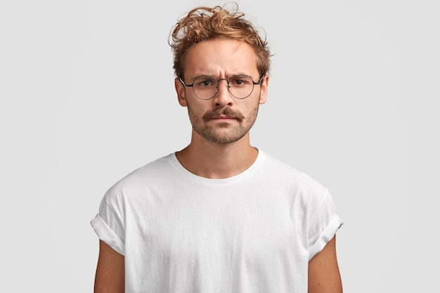 Foto interna de um homem sério com expressão mal-humorada, descontente com vizinhos barulhentos, vestido com uma camiseta branca casual e óculos, poses internas