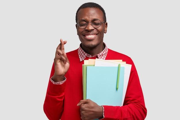 Foto interna de um homem sorridente de pele escura cruza os dedos, acredita na boa sorte e fortuna, segura documentos, escreve com caneta, vestido com um macacão vermelho