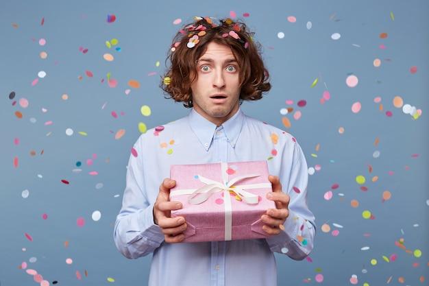 Foto interna de um homem surpreso que recebeu um presente de ano novo