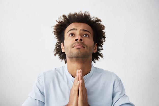 Foto interna de um jovem afro-americano religioso desesperado com cabelo despenteado