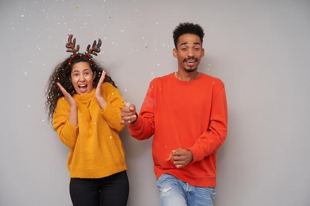 Foto interna de um jovem alegre casal de cabelos escuros cacheados fazendo confete com badalo durante a comemoração do ano novo, vestindo suéteres coloridos de lã aconchegantes e uma cesta de natal sobre fundo cinza