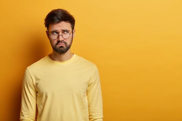Foto interna de um jovem barbudo chateado parece com uma expressão miserável à parte, pensa em algo, tem uma aparência triste e infeliz, usa óculos óticos e macacão casual, posa dentro de casa sobre uma parede amarela