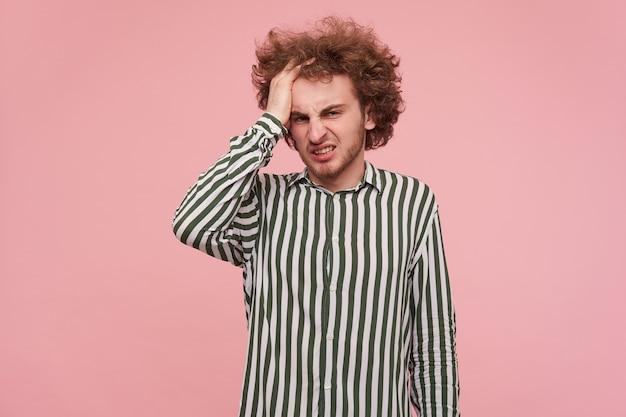 Foto interna de um jovem barbudo descontente segurando seu cabelo ruivo encaracolado com a mão levantada e olhando para a câmera com beicinho, vestindo uma camisa listrada sobre a parede rosa