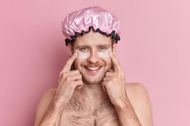 Foto interna de um jovem bonito e sorridente com a barba por fazer indica manchas de hidrogel sob os olhos