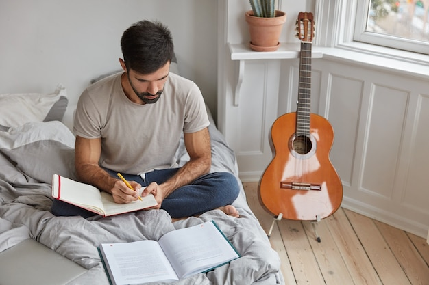 Foto interna de um jovem com a barba por fazer sentado em posição de lótus na cama desarrumada