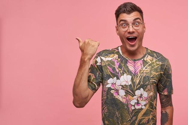 Foto interna de um jovem de cabelos curtos animado, usando óculos e uma camiseta florida, olhando alegremente com expressão de surpresa no rosto, isolado