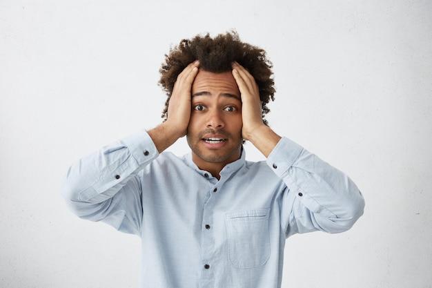 Foto interna de um jovem de pele escura assustado com as mãos na cabeça