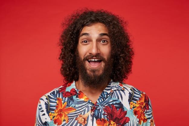 Foto interna de um jovem feliz, morena, barbudo, com cachos, olhando alegremente para a câmera com um grande sorriso, estando em alto astral enquanto posava sobre um fundo vermelho, vestido com uma camisa florida multicolorida