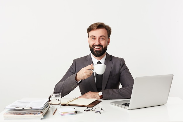 Foto interna de um jovem homem barbudo e positivo, tendo um bom dia de trabalho e sorrindo alegremente para a frente enquanto está sentado à mesa na parede branca, segurando uma xícara de café durante o intervalo