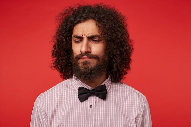 Foto interna de um jovem homem cacheado de cabelos escuros descontente com uma barba luxuriante franzindo as sobrancelhas enquanto olha severamente para baixo, em pé contra um fundo vermelho em roupas formais
