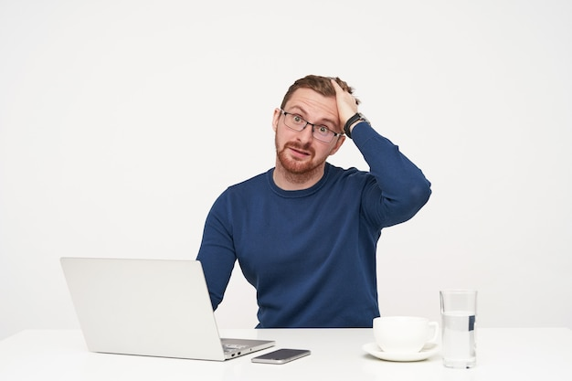 Foto interna de um jovem perplexo e barbado, de cabelos claros, segurando a cabeça com a mão levantada enquanto olha perplexo para a câmera, posando sobre um fundo branco
