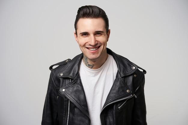 Foto interna de um jovem roqueiro com um sorriso atraente