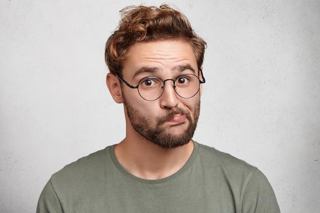 Foto interna de um jovem suspeito curva os lábios, usa óculos, hesita