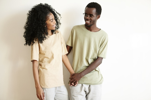 Foto interna de um lindo jovem casal africano vestido casualmente, descansando juntos em casa, segurando as mãos um do outro e sorrindo alegremente