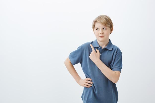 Foto interna de um menino bonito intrigado com cabelo loiro, erguendo sobrancelhas com expressão curiosa e segurando a mão no quadril
